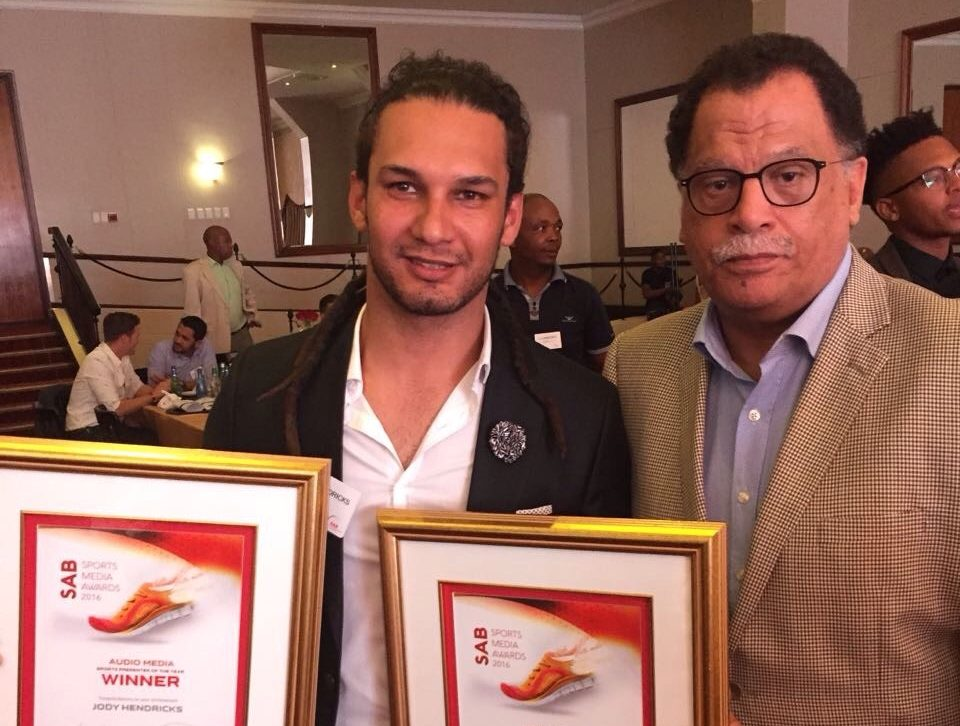 Jody Hendricks poses with his new awards with Danny Jordaan, Just Jody